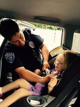 Little Ellen getting her car seat adjusted by Officer Judy Racow