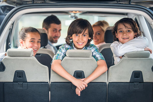 Playful kids posing in the back of a car with their parents in background and 10 tips on what not to leave in a hot car