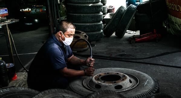 Am I liable if my employee states they caught COVID at work?  Worker sitting on the floor working on a tire and wearing a mask.  Photo courtesy of Kasarin Naipongprasit on Unsplash