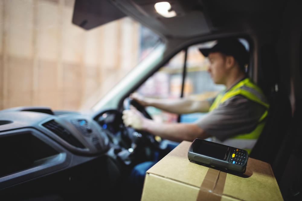 DVS Driver Verification System showing a Delivery driver driving van with parcels on seat outside warehouse